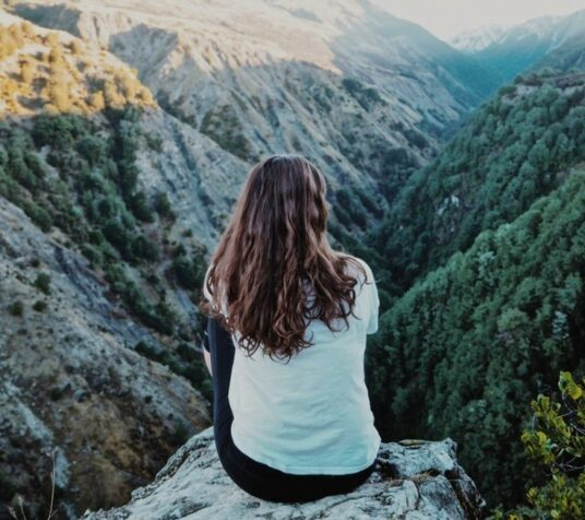Woman sitting on rock looking out over the mountains