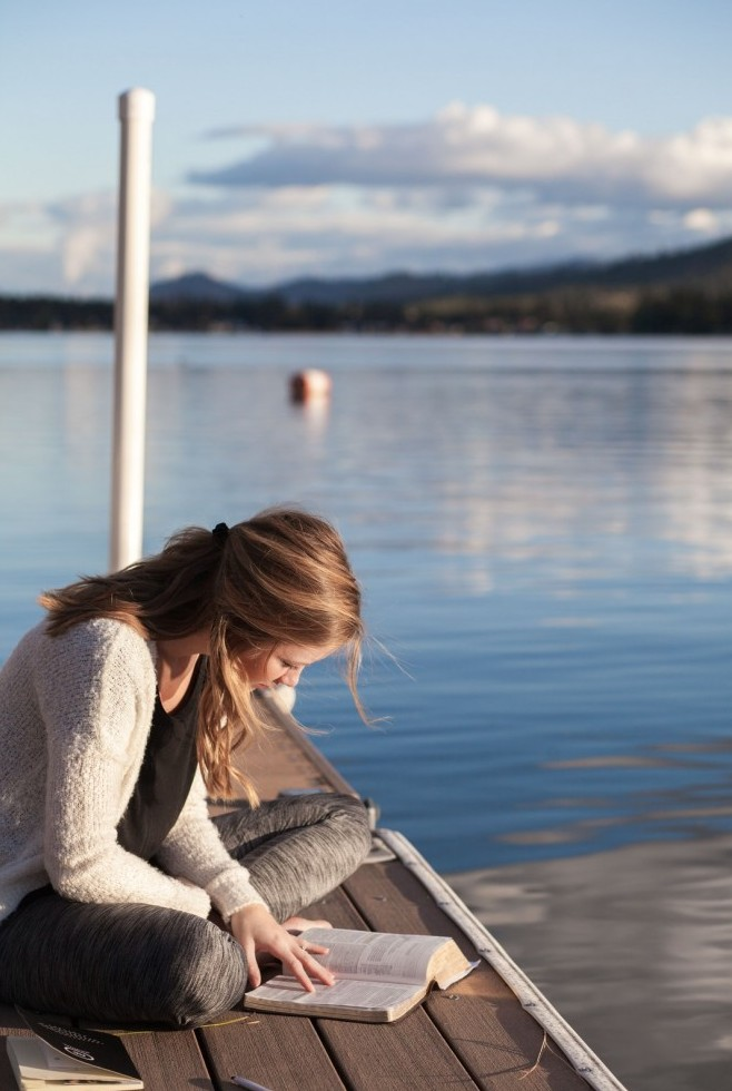 woman reading Bible on pier