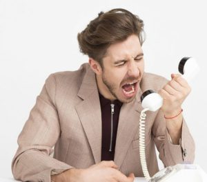 Young business man screaming into office phone