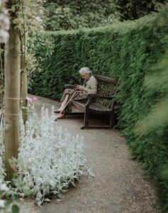 Older woman with cane sitting on bench