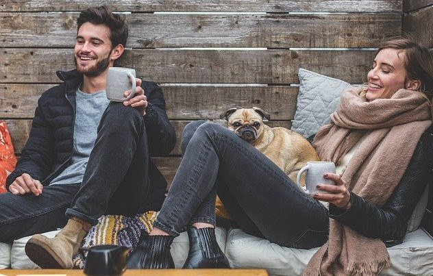 Man & woman laughing & drinking coffee with dog
