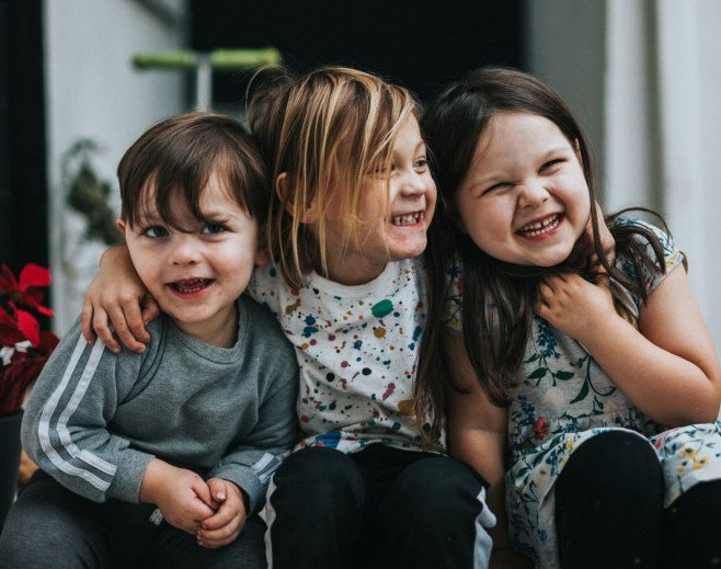 3 children sitting together laughing