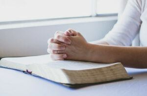 Woman with hands folded on open Bible