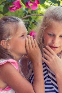 Young girl whispering in ear of girl